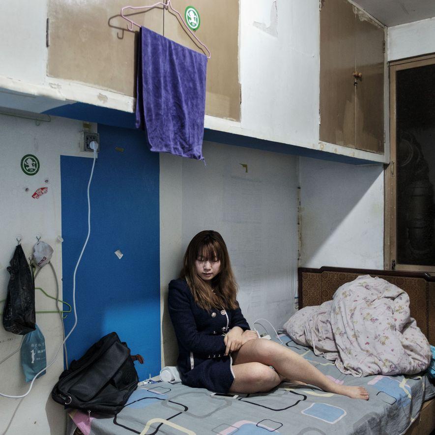 Xian, de 23 años, sentada en la cama de su habitación en el refugio atómico Nong ...