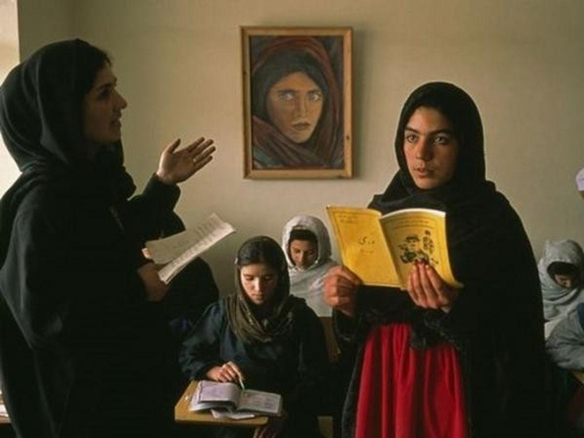 Una niña afgana lee durante una clase. El retrato del fondo es la famosa portada de la …