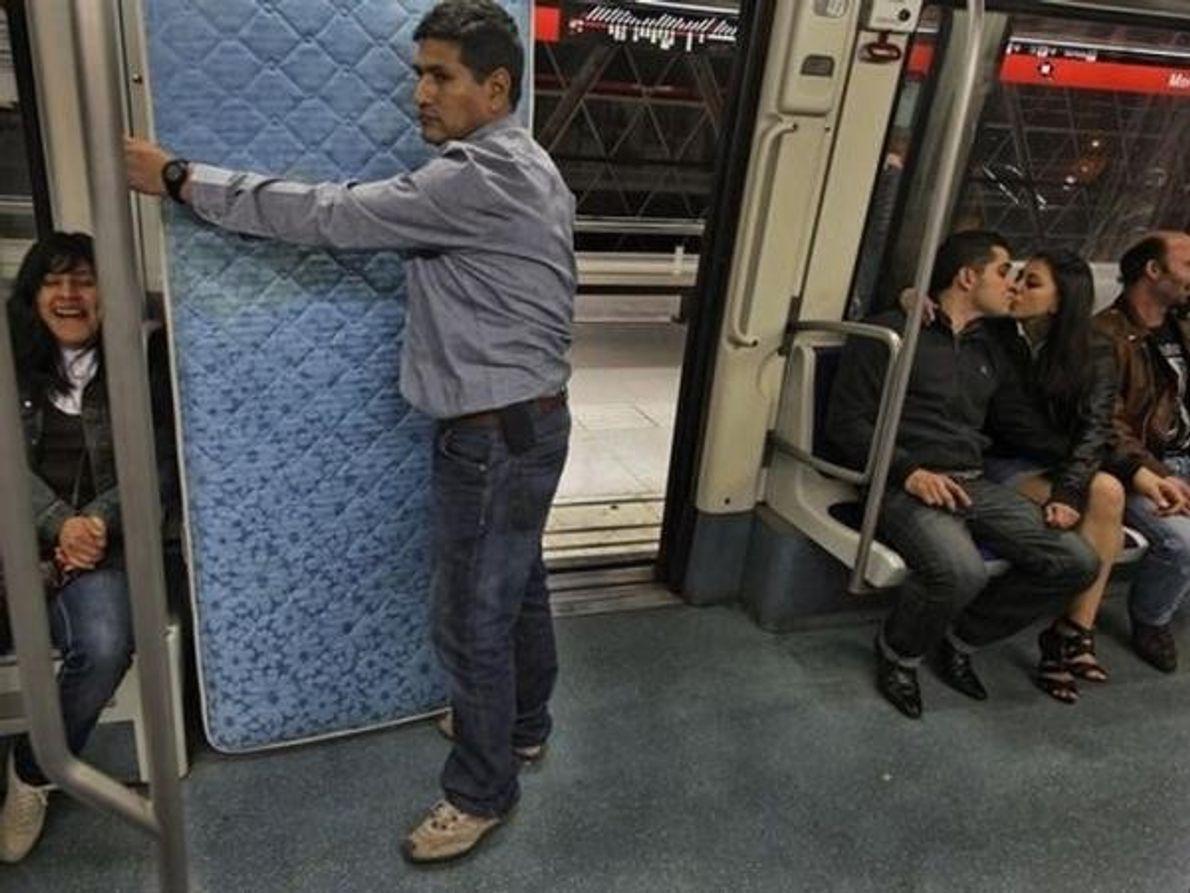 Una pareja se besa en el metro de Barcelona.