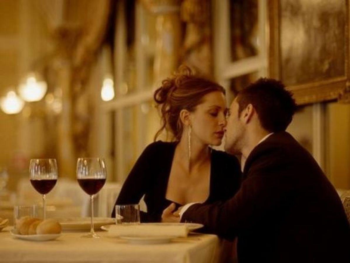 Una pareja se acerca para compartir un beso en un restaurante de Milán (Italia).