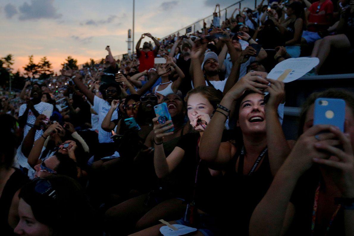La gente contempla el eclipse solar desde un estadio de fútbol americano en la Universidad del …
