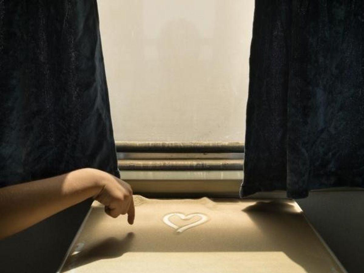 Niño dibuja un corazón en la arena