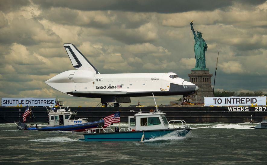 El transbordador espacial Enterprise, colocado sobre una barca, pasa frente a la Estatua de la Libertad ...