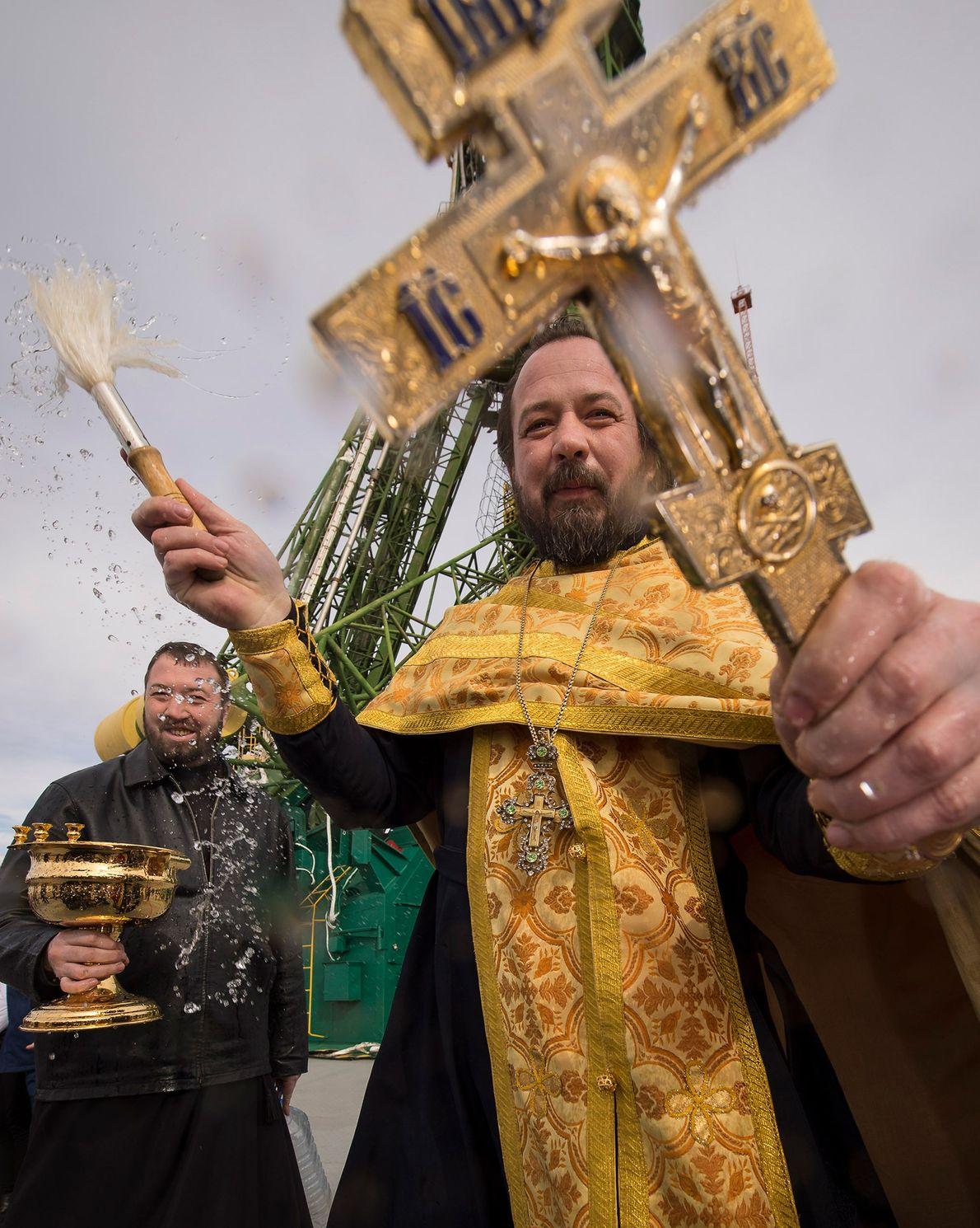 Un sacerdote ortodoxo bendice a los medios junto al cohete Soyuz en la plataforma de lanzamiento …