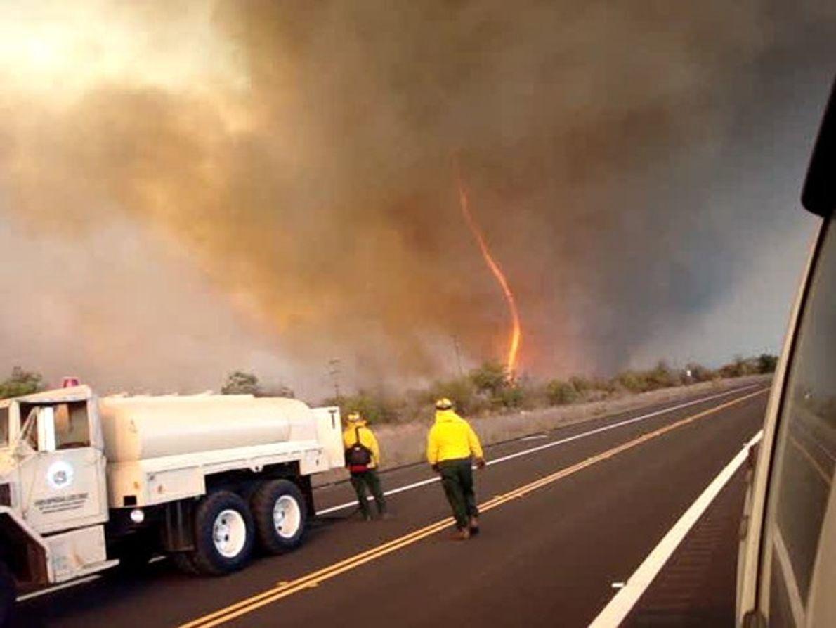 Bomberos luchan contra un tornado de fuego cerca del volcán de Mauna Kea, al sur de …