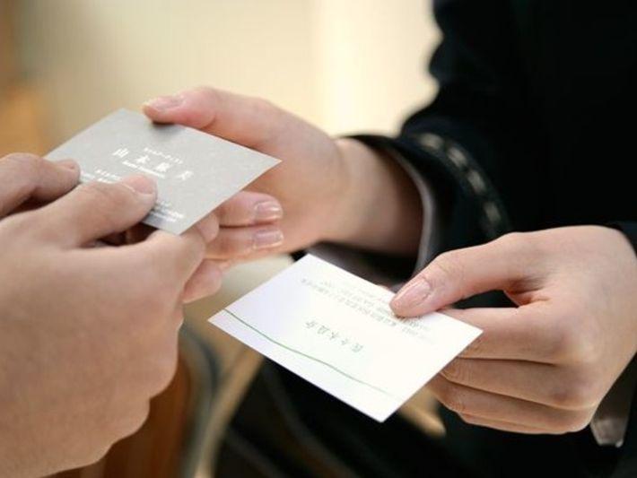 Dos personas intercambian tarjetas de presentación con texturas distintas (foto de archivo).