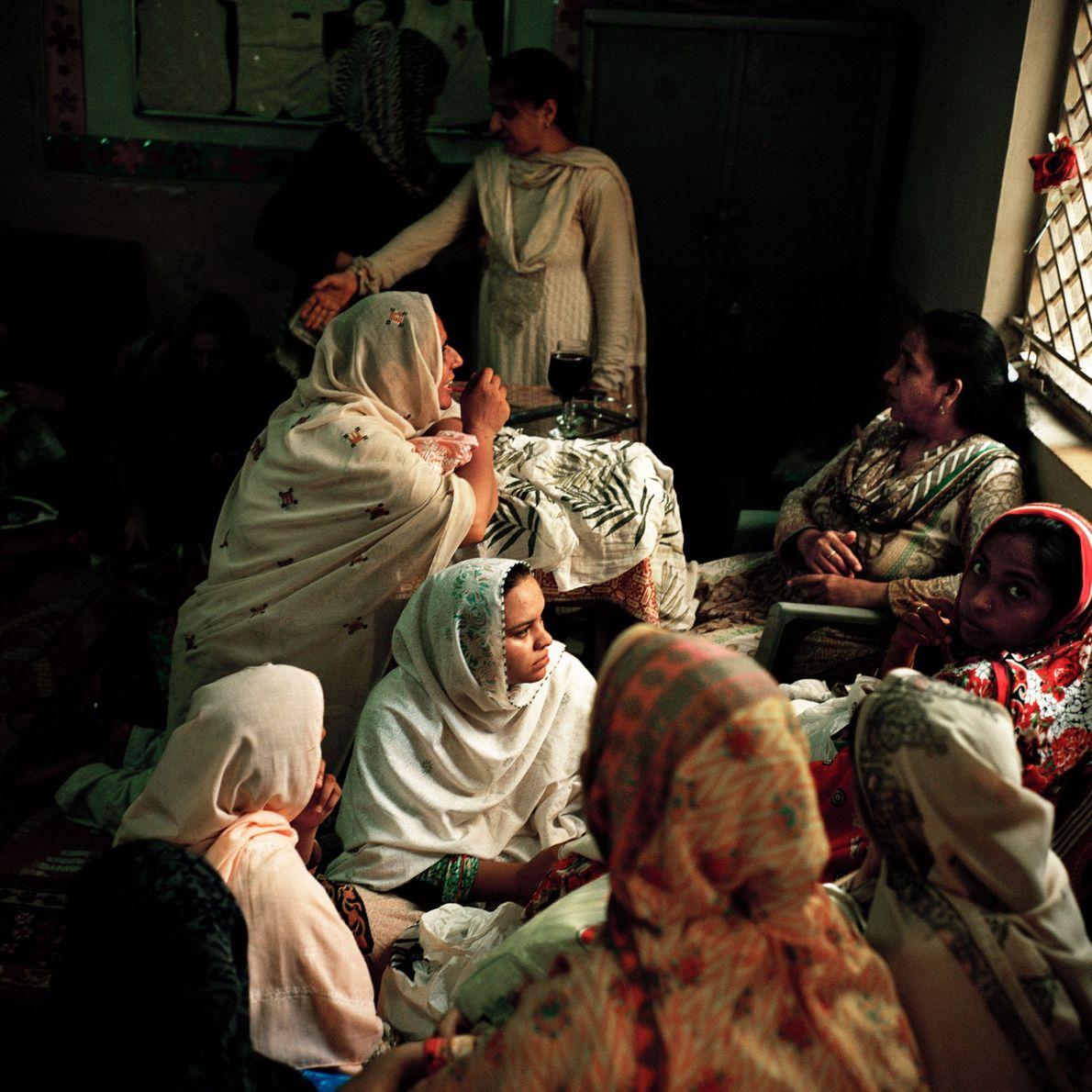 Las mujeres muestran sus tejidos bordados a mano a Tasleem Akhtar, de 55 años, que dirige …