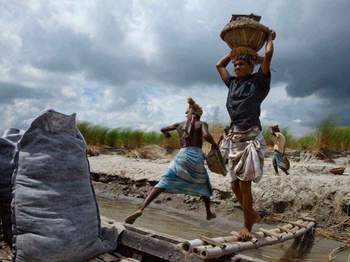 Barqueros cargando arena