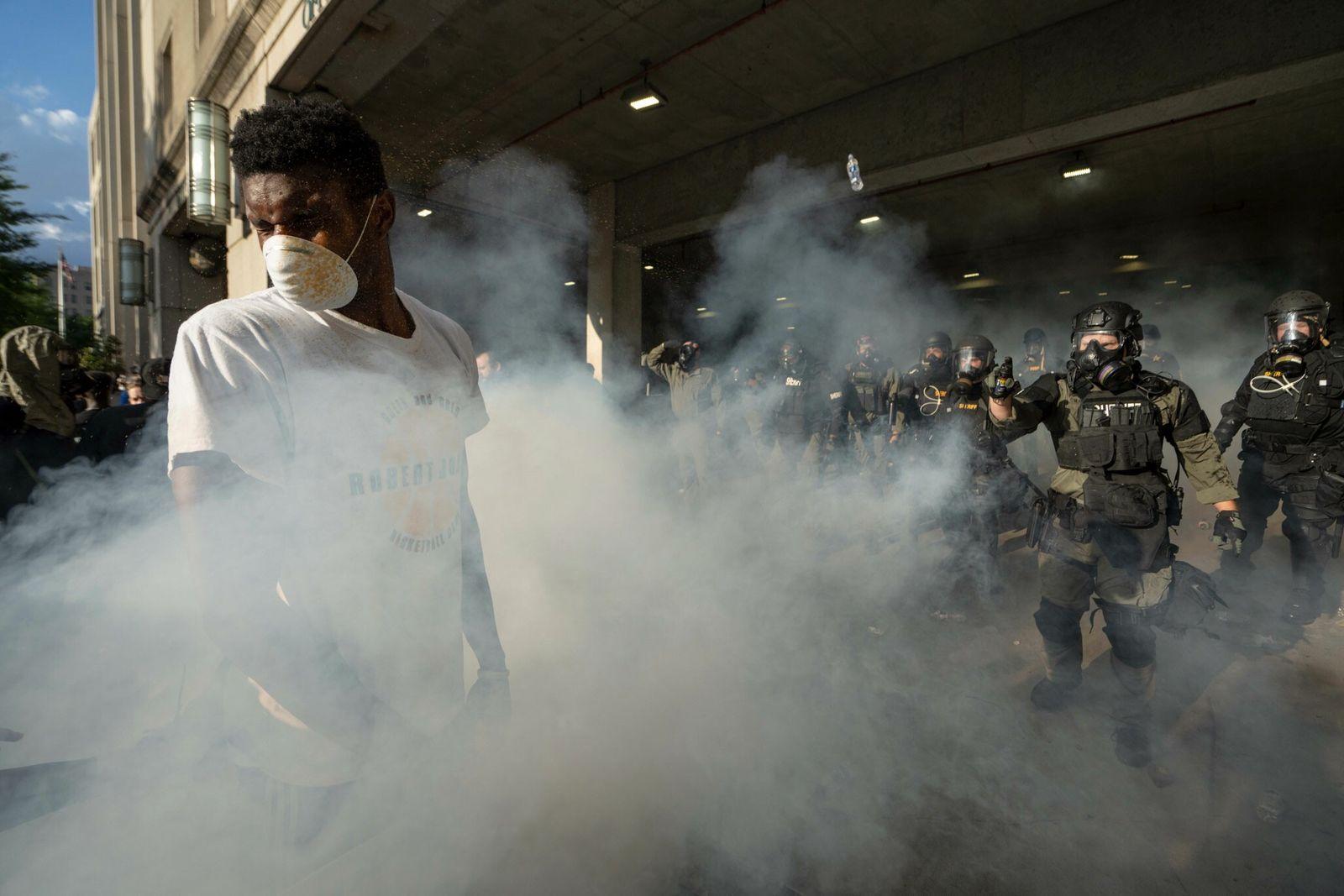 Un manifestante envuelto enuna nube de gas lacrimógeno