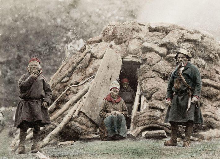 Fotografía de unos samis frente a una vivienda tradicional
