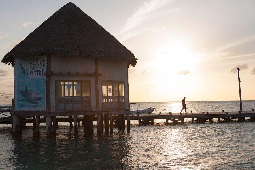 El sol se pone sobre un embarcadero en isla Holbox. Aunque se propuso un gran proyecto urbanístico hace poco, los pescadores han conservado su derecho a usar la playa, impidiendo así la construcción de hoteles.
