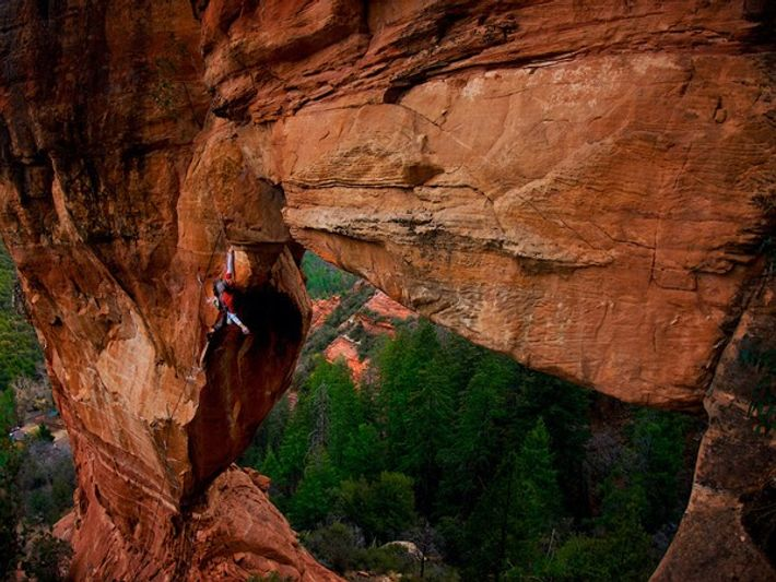 Escalador colgado de una roca roja