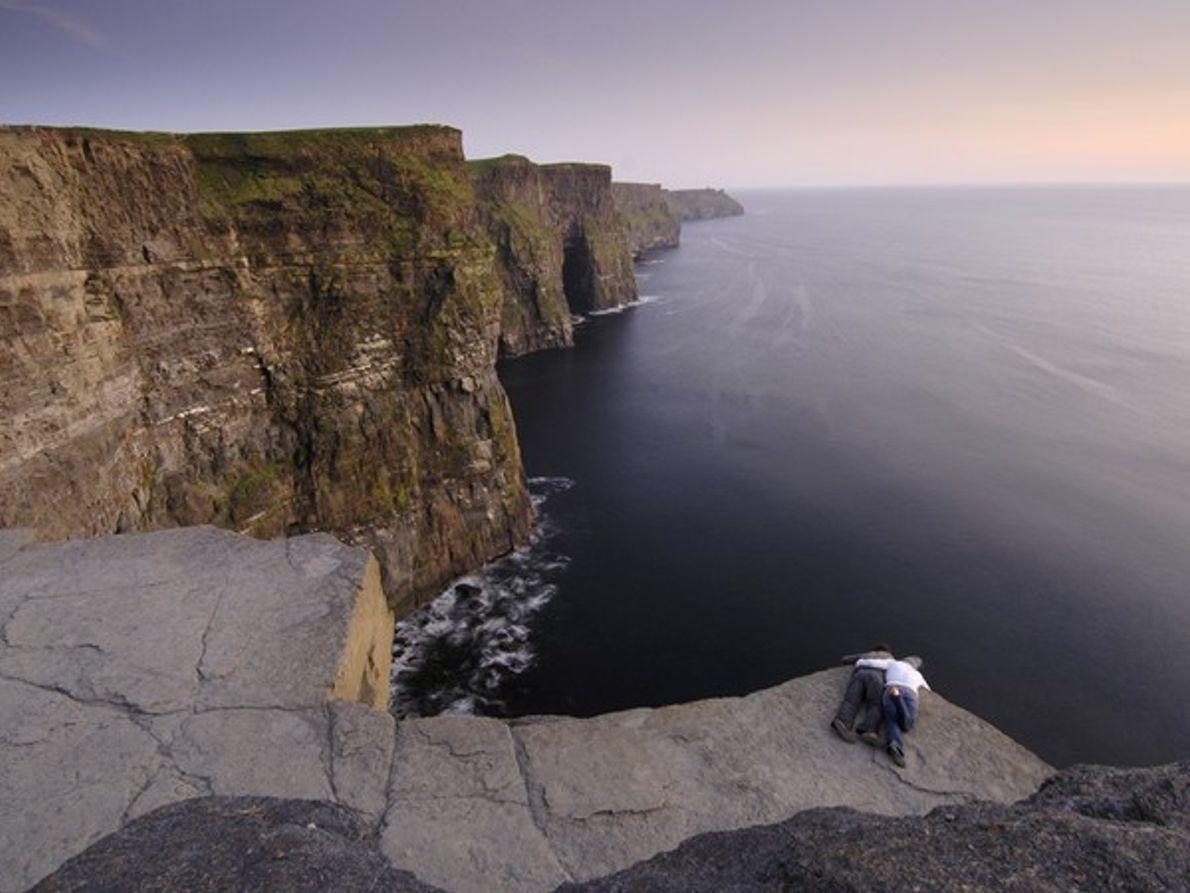 Una pareja observando el océano desde un acantilado rocoso
