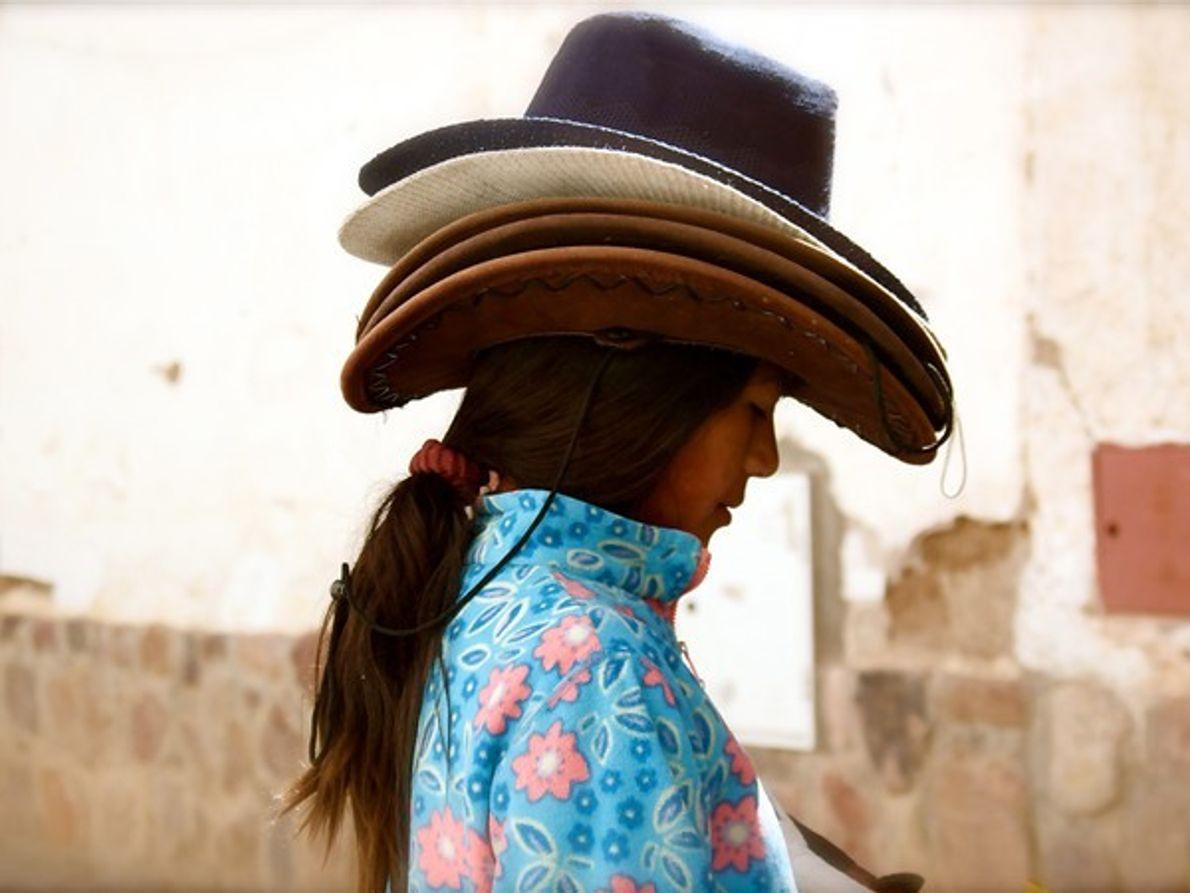 Niña llevando varios sombreros de cowboy