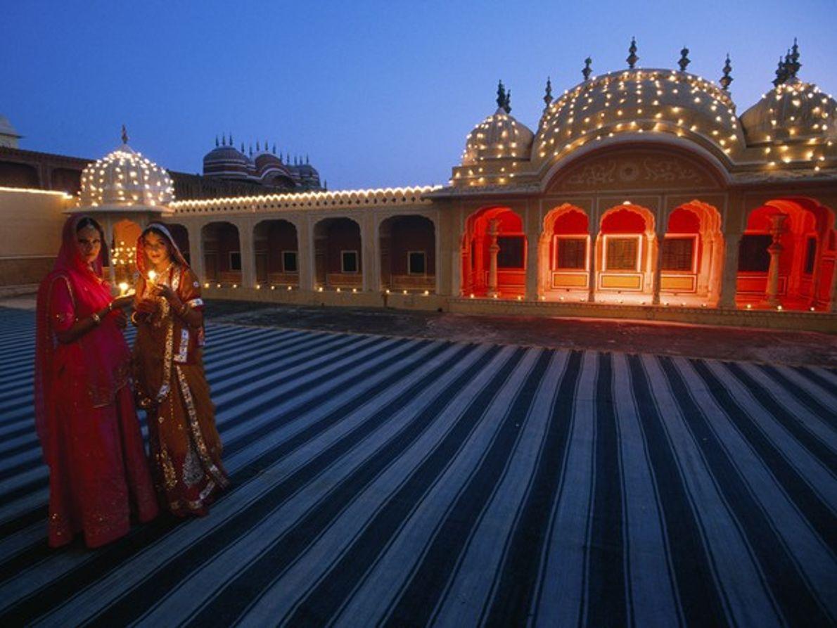 Mujer sujetando velas frente un palacio iluminado