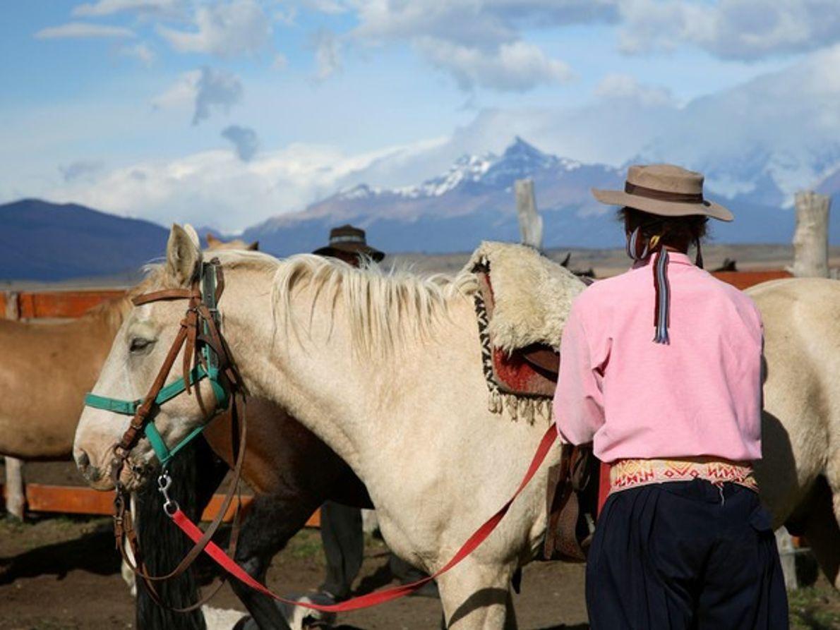 Hombre y caballos reposando bajo las montañas