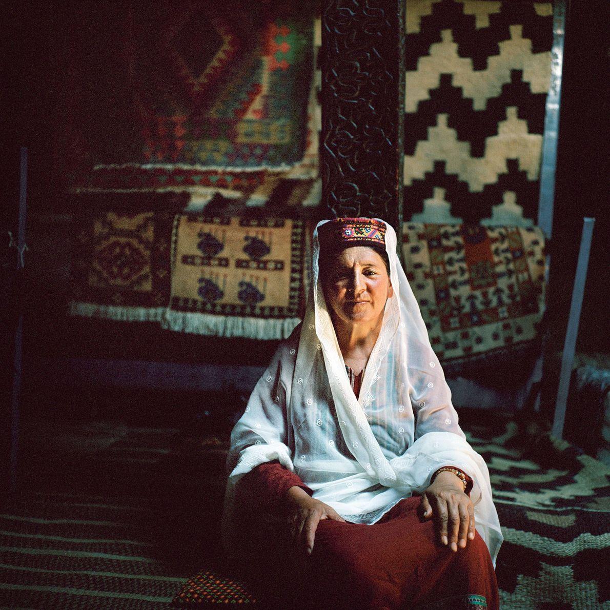 Zina Parvwen, de 52 años, junto a diversas alfombras wakhi tradicionales que ella y otras once …