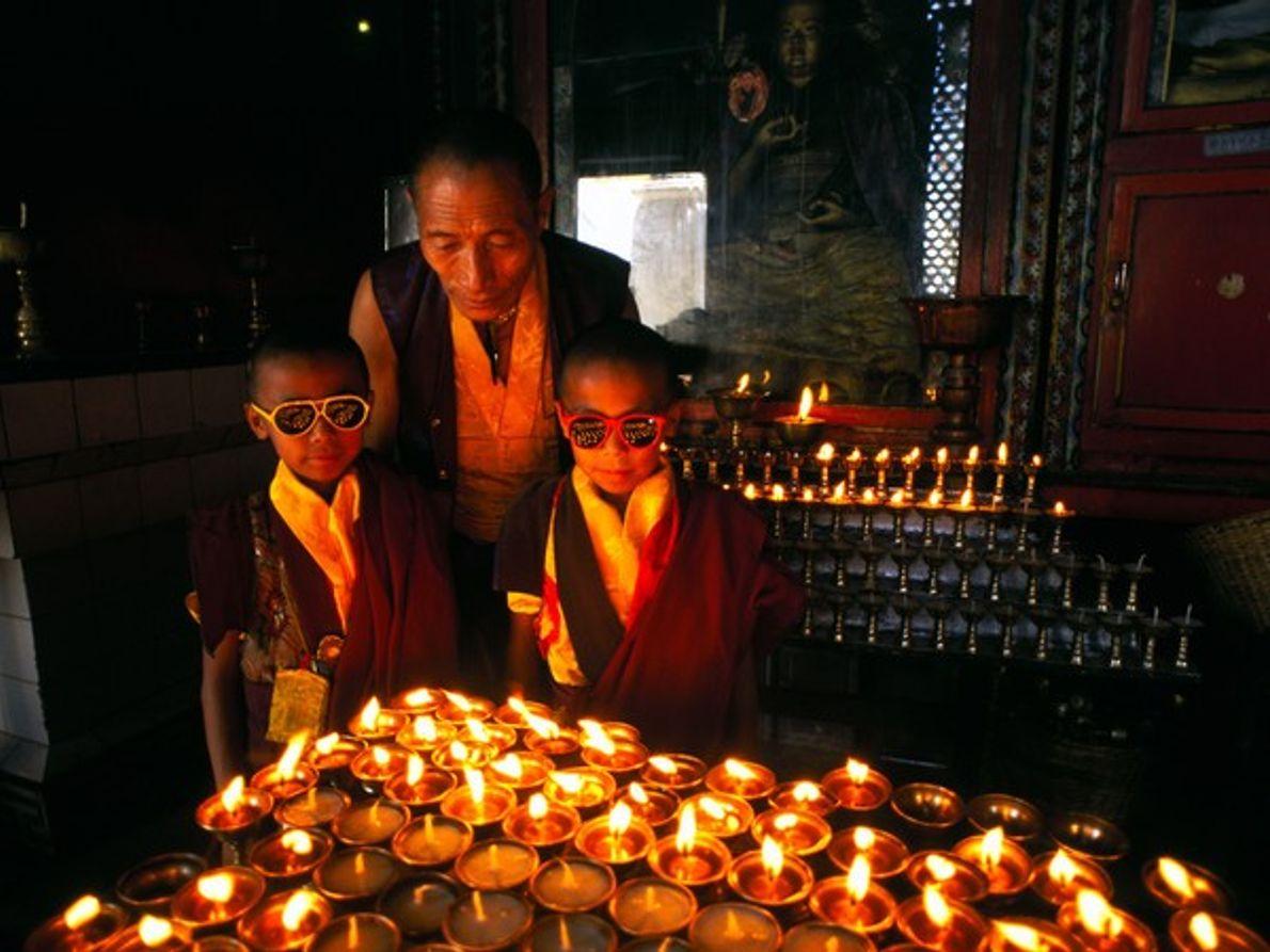 Monjes dentro de un templo con lámparas de mantequilla