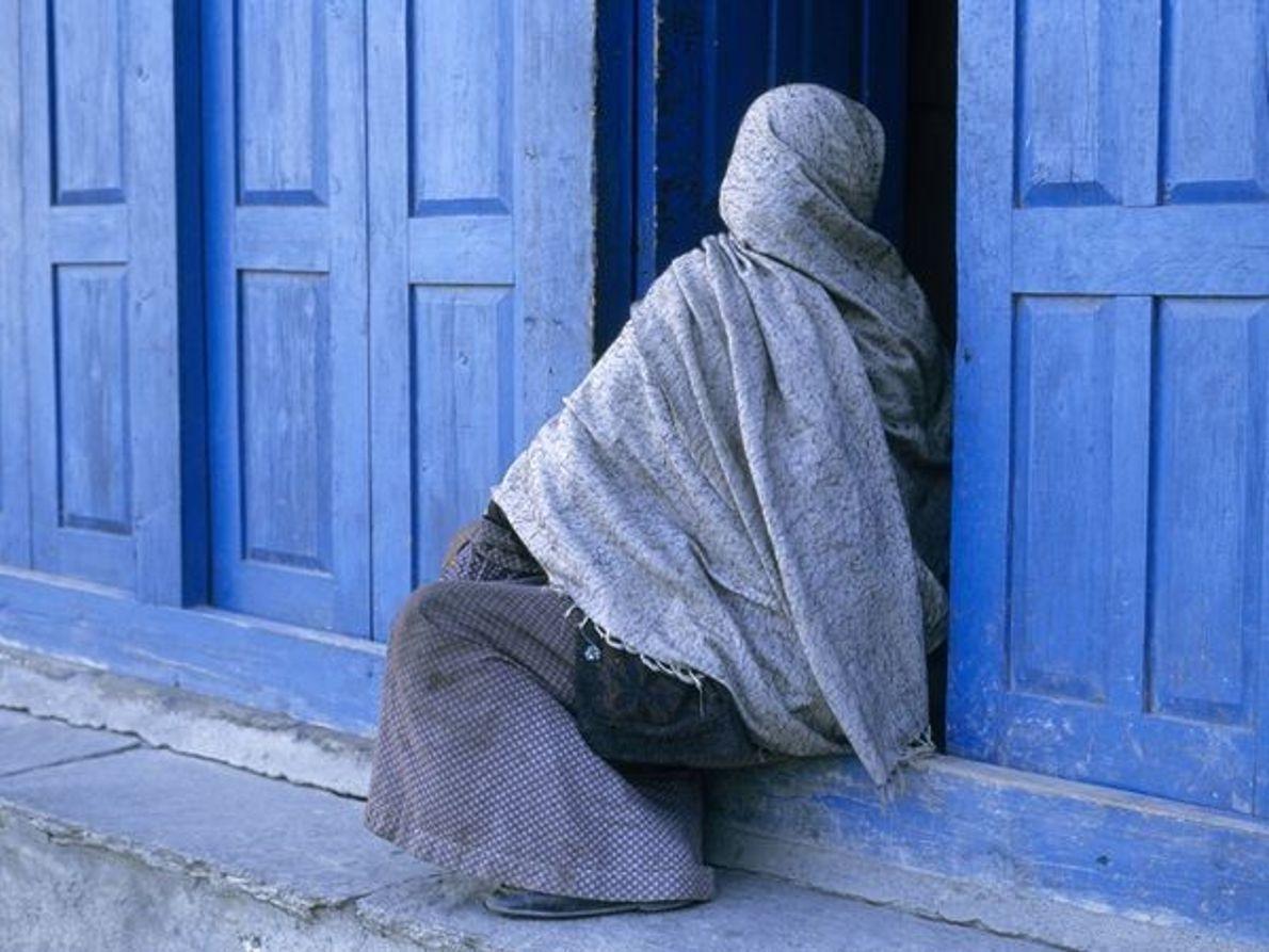 Mujer con velo sentada en un portal.