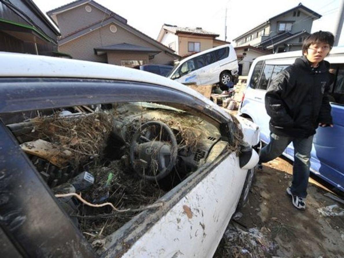 Un niño camina atravesando un grupo de vehículos dañados por el terremoto y posterior tsunami en …