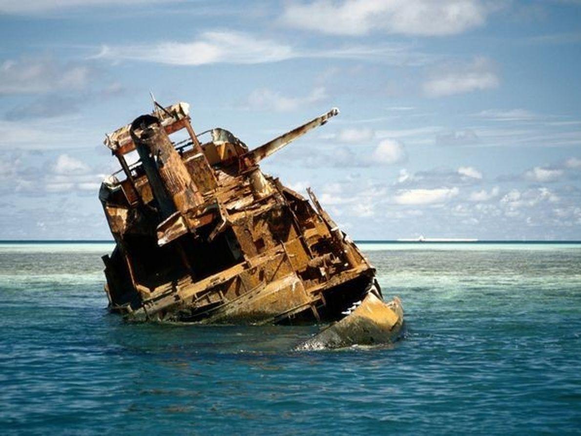 El casco oxidado de un barco yace en las aguas poco profundas del arrecife de Tubbataha …