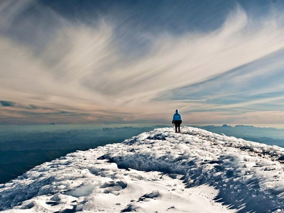 Mujer de pie en la cima de un cráter