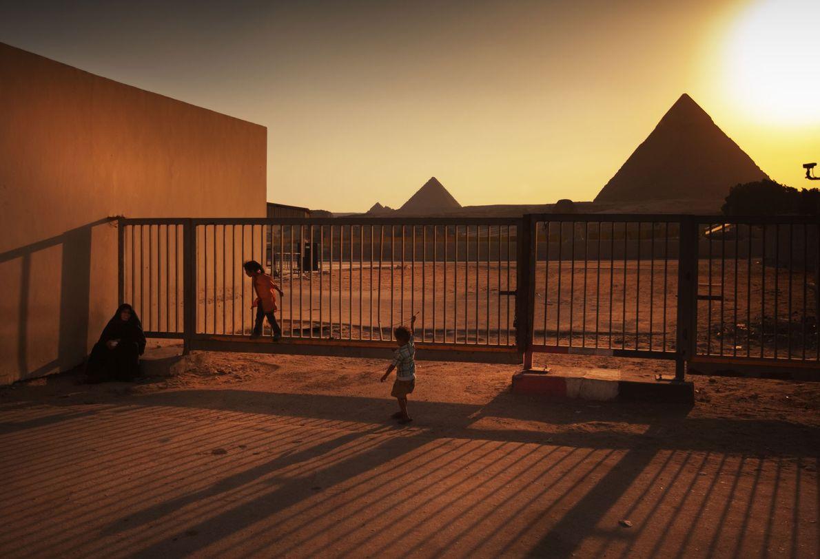 Unos niños juegan en la puerta de acceso a las pirámides de Guiza.