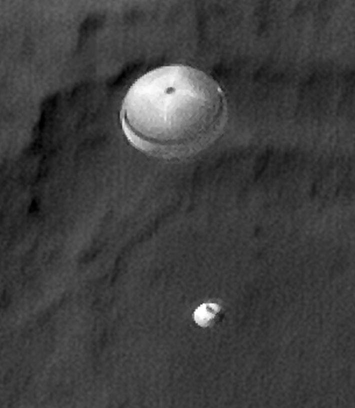 El rover Curiosity de la NASA desciende con el paracaídas desplegado, en una fotografía tomada por ...