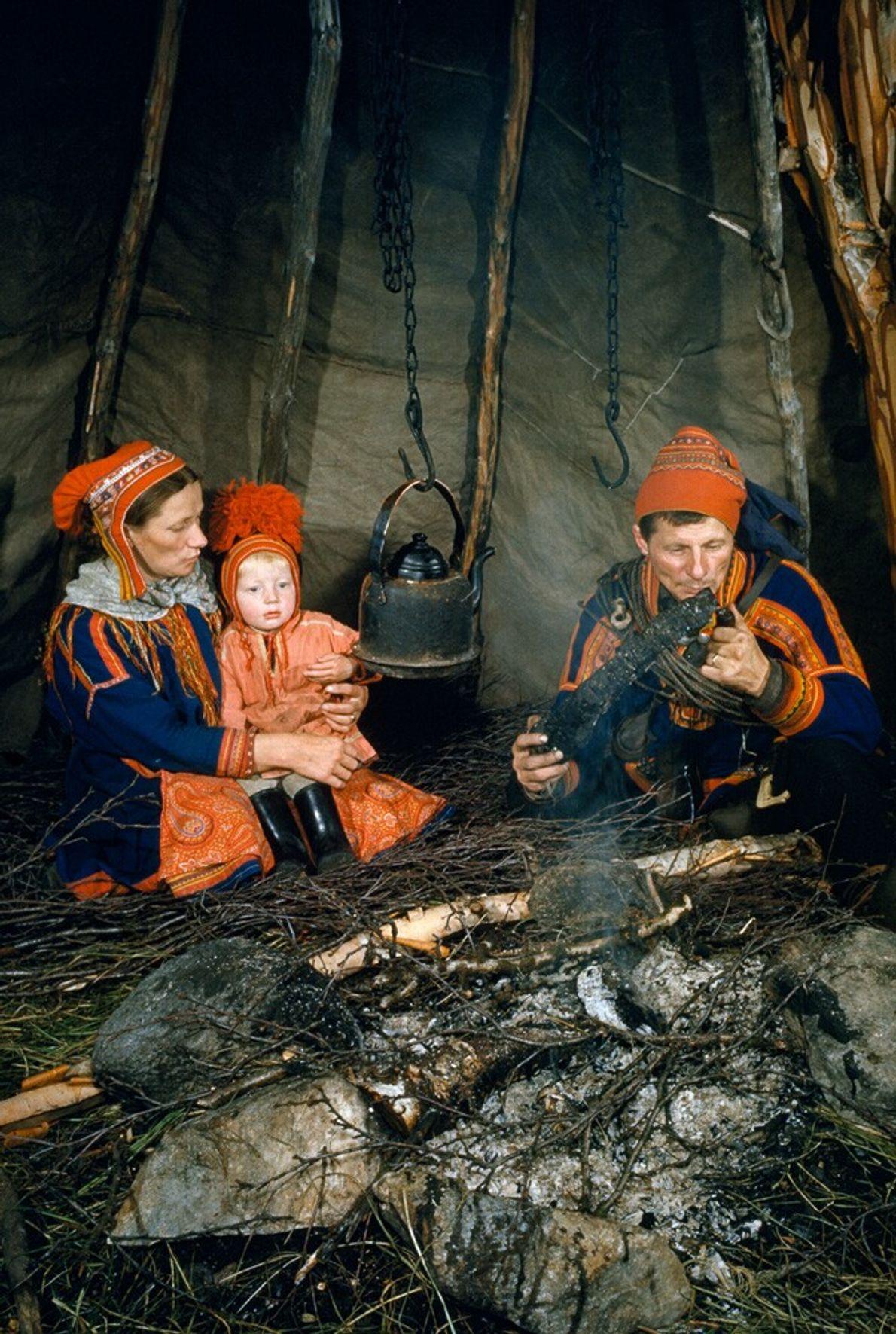 Familia sami sentada alrededor de una hoguera