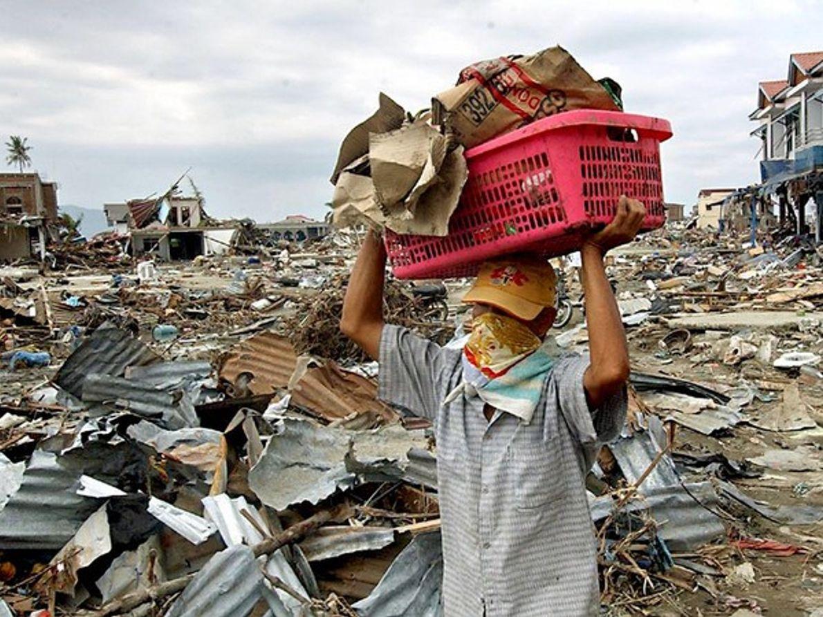 Hombre cargando con sus posesiones tras el tsunami