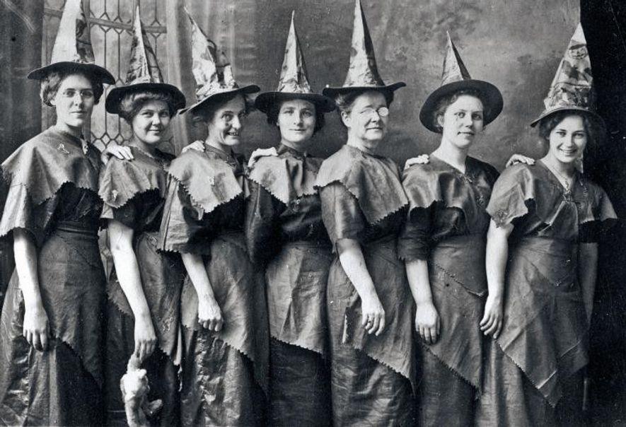 """Un aquelarre de """"brujas"""" disfrazadas en un retrato de Halloween en 1910."""