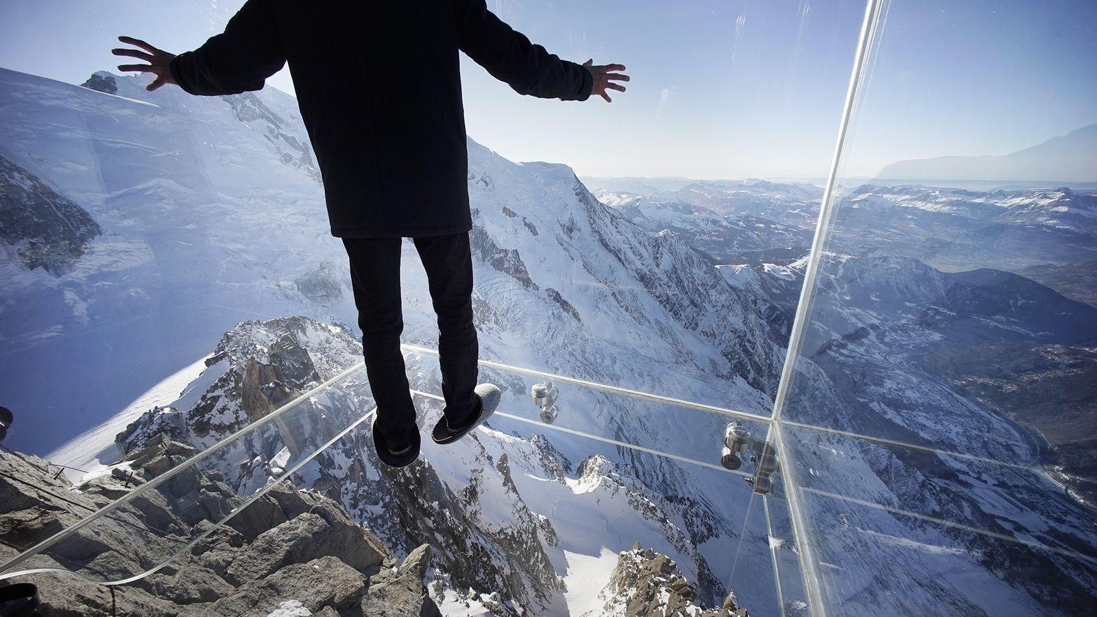 Foto de un periodista en la caja de cristal sobre los Alpes Franceses