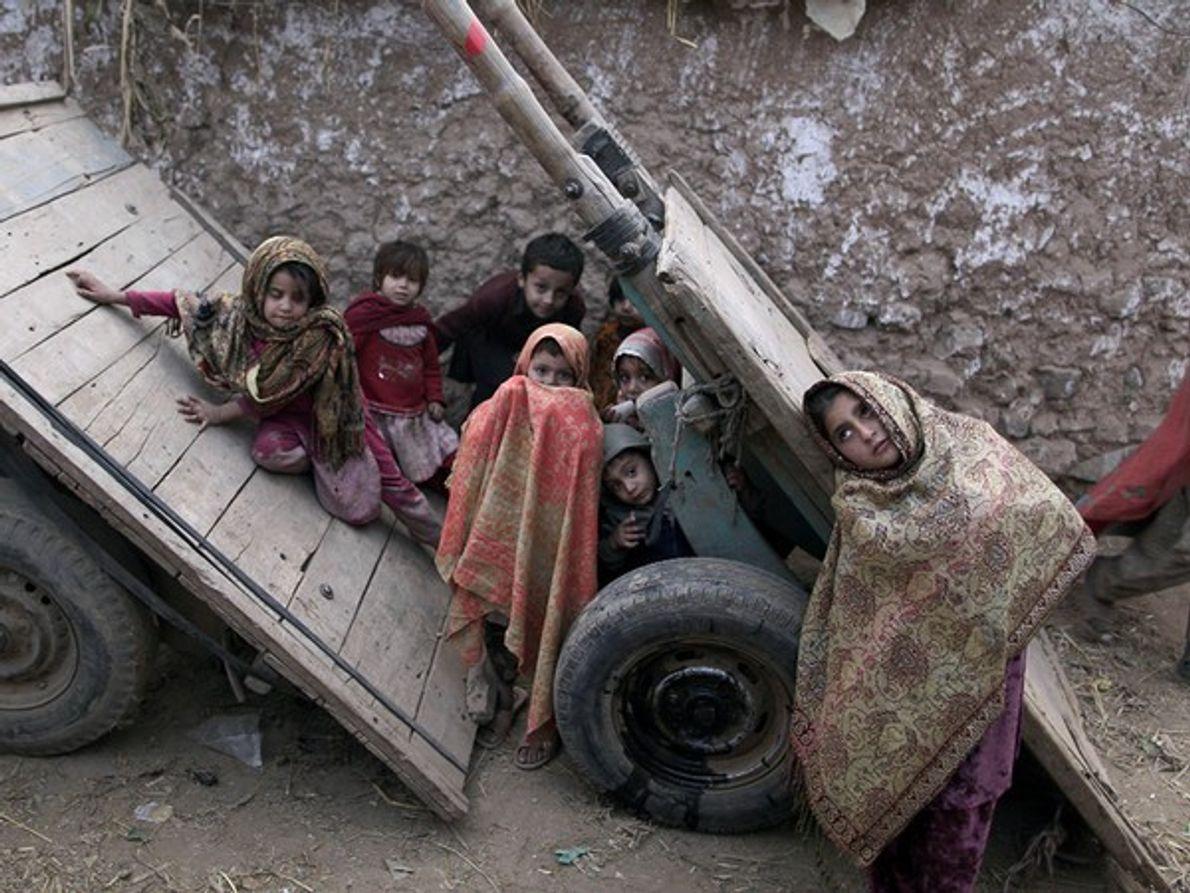 Niños Afganos refugiados juegan en el callejón de un barrio de las afueras de Afghan Islamabad, …