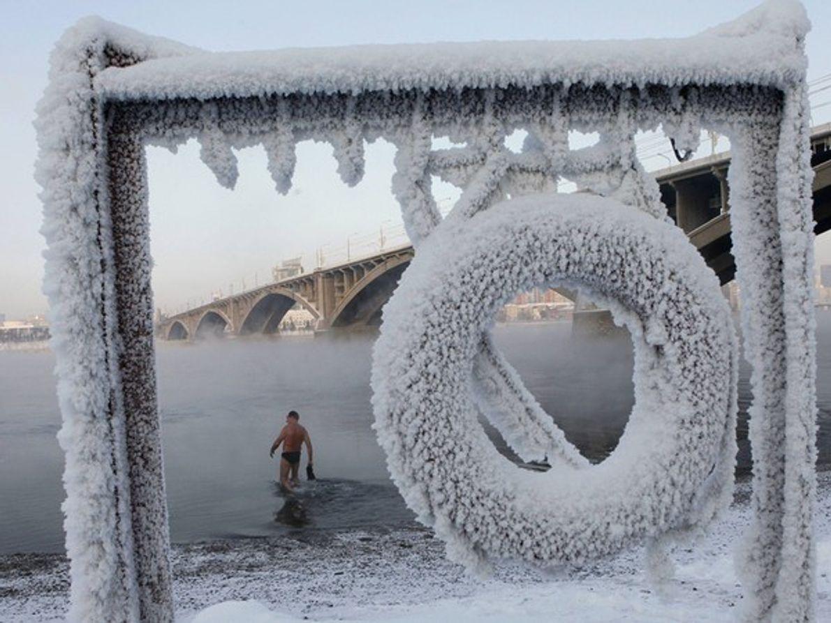 A una temperatura de 20 grados bajo cero, un miembro de un club de natación invernal …