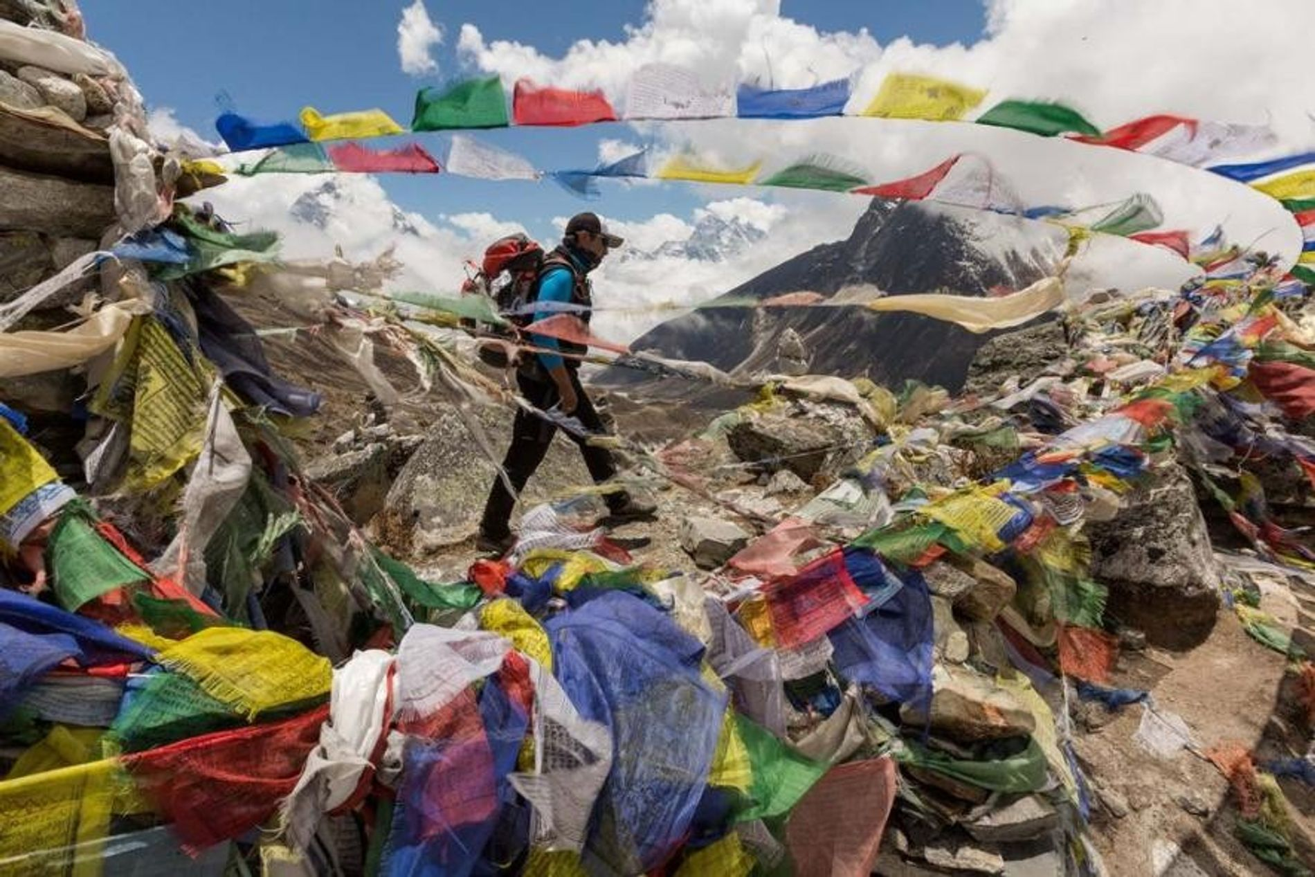 Durante su ascenso al monte Everest, el sherpa Mingma Ongel pasa delante de banderas con plegarias en un memorial para los sherpas que murieron en el pico. Desde las primeras expediciones en la década de 1920, 99 sherpas y otros nepalís han muerto en el Everest, lo que supone un 40 por ciento de todas las muertes durante la escalada en esta montaña.