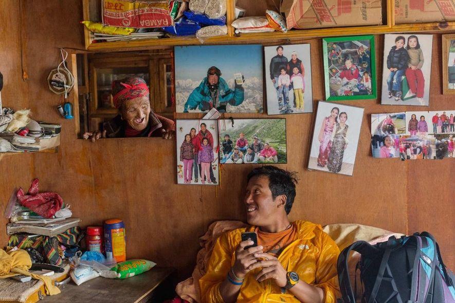 Danuru Sherpa se ríe con su madre, Daki Sherpa, en su hogar en la aldea de Phortse, en la región del Everest. Danuru, que ha encumbrado el Everest 16 veces, vive parte del tiempo con su madre y parte en Katmandú con su mujer y sus hijos, cuyas fotos decoran la pared tras él. Ocho de los hijos de Daki han trabajado como guías de montaña.