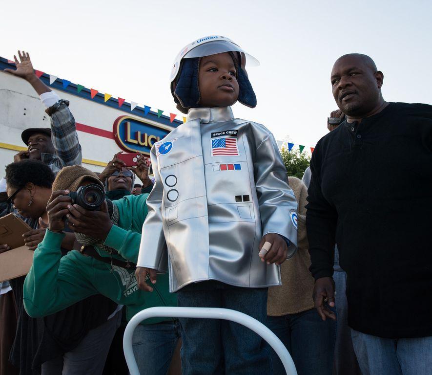 Vestido de astronauta, un joven espectador observa el transbordador espacial Endeavour en camino a su nuevo ...