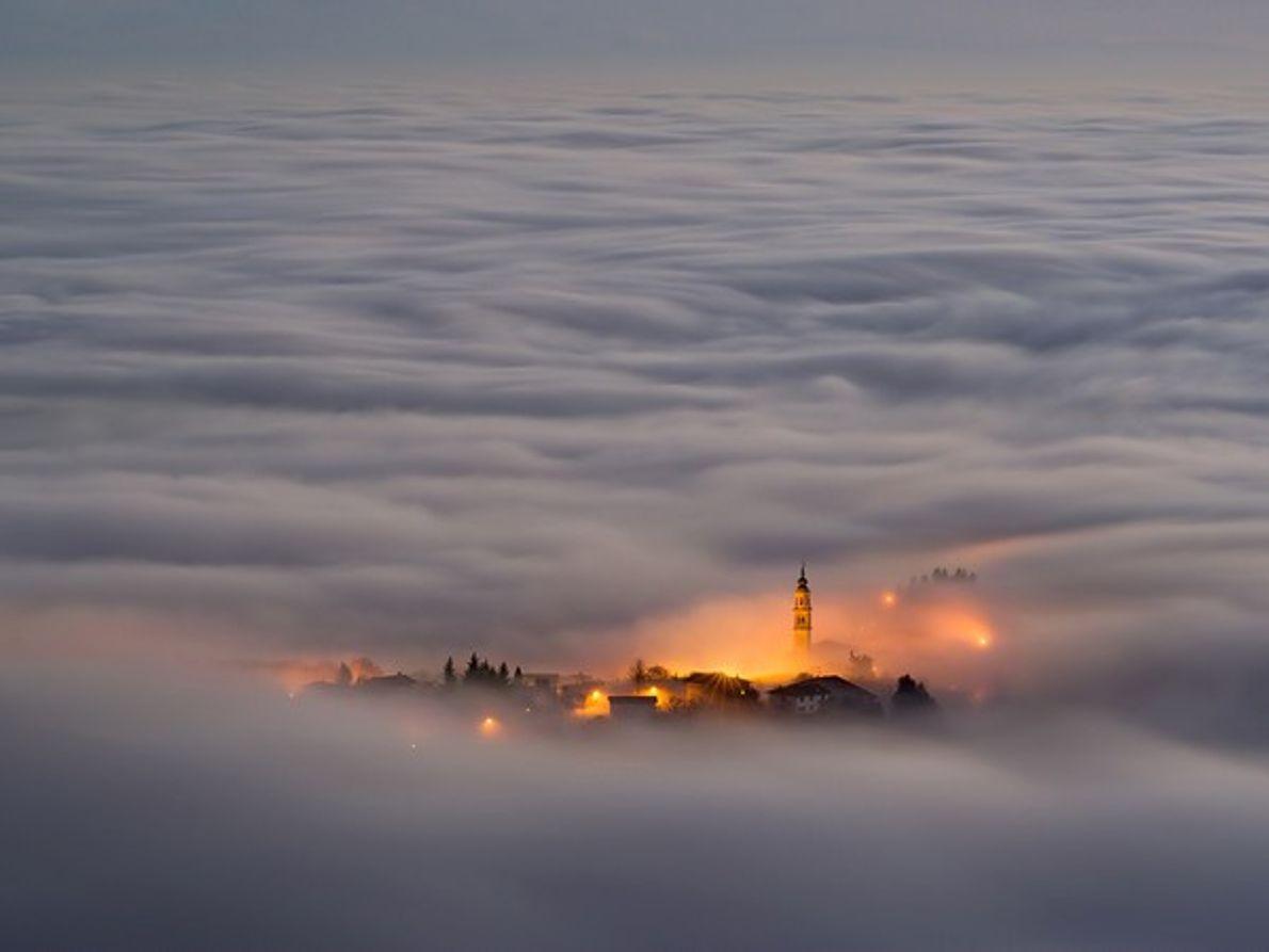 Un pueblo de montaña en Italia envuelto en la niebla.