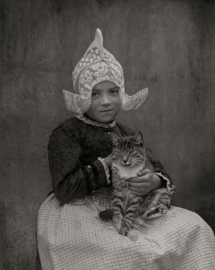Una niña en la década de 1920 en Volendam, Países Bajos, acuna a su gato.