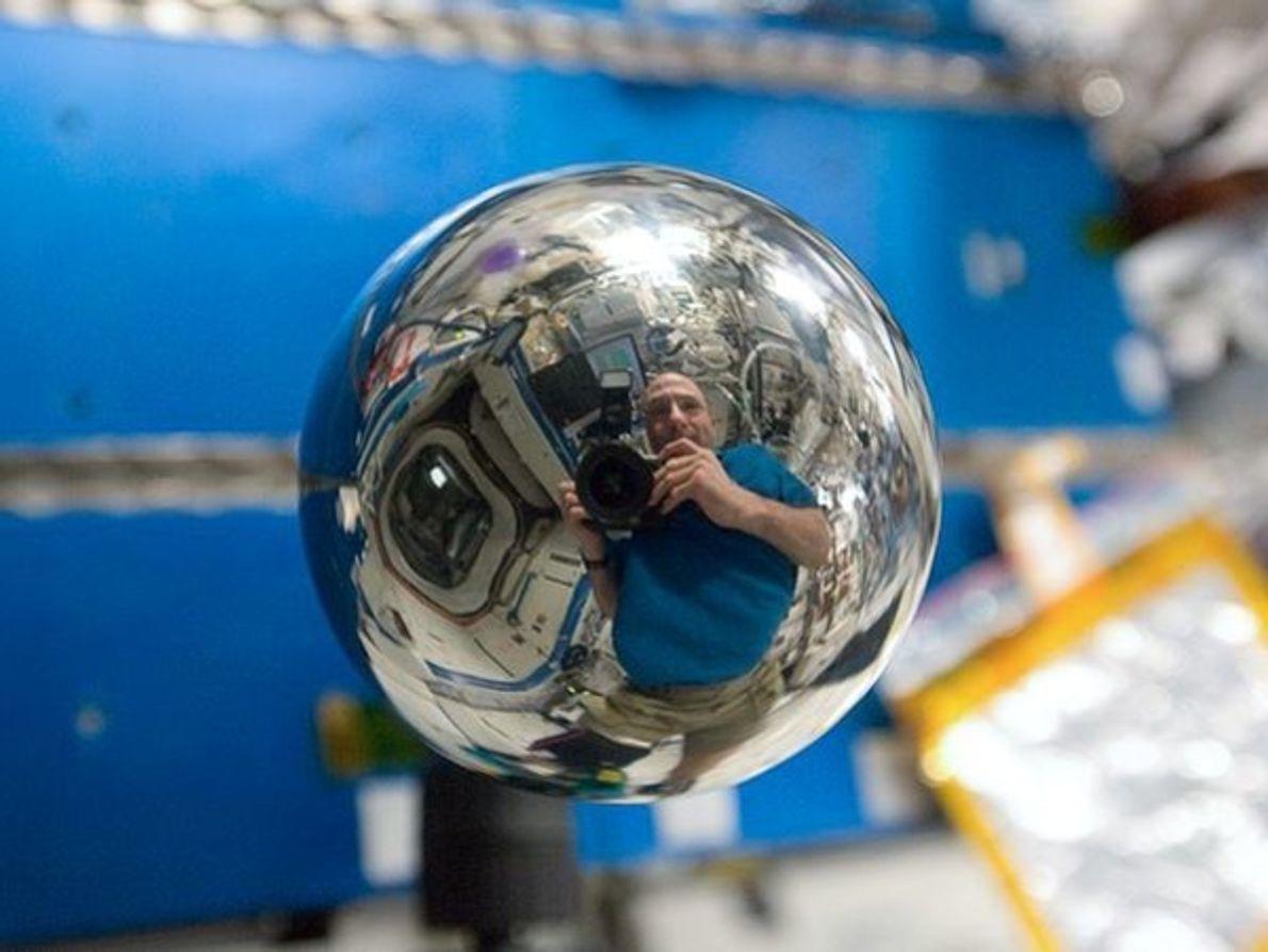 Astronauta de la NASA Don Pettit se refleja en una esfera de metal en la Estación …