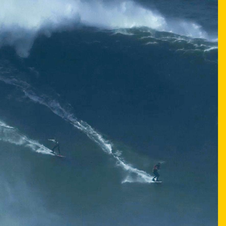 Dos surfistas se deslizan a la vez sobre una ola gigantesca en Praia do Norte