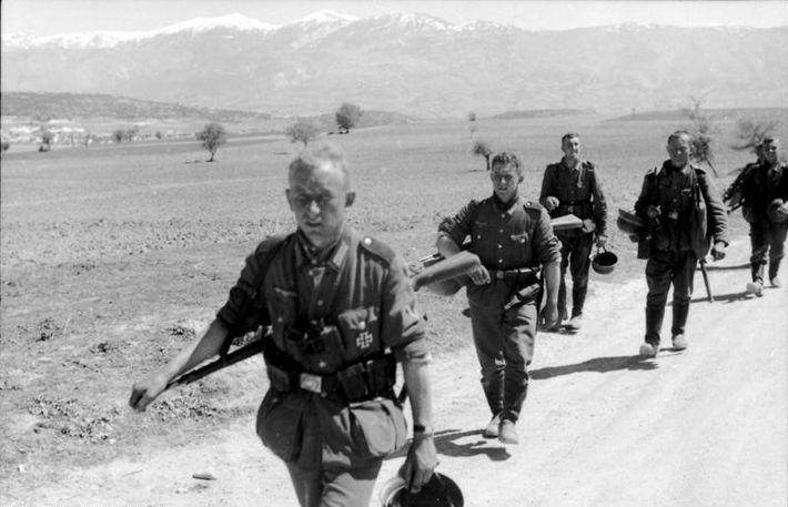 Soldados alemanes con el casco de acero quitado durante una marcha en terreno llano, con las ...