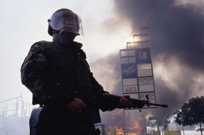 Un miembro de la Guardia Nacional  custodia un edificio en llamas en Los Ángeles.