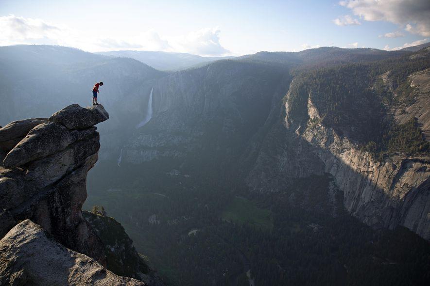 Alex Honnold mira por encima del borde de Glacier Point en el Parque Nacional de Yosemite. …