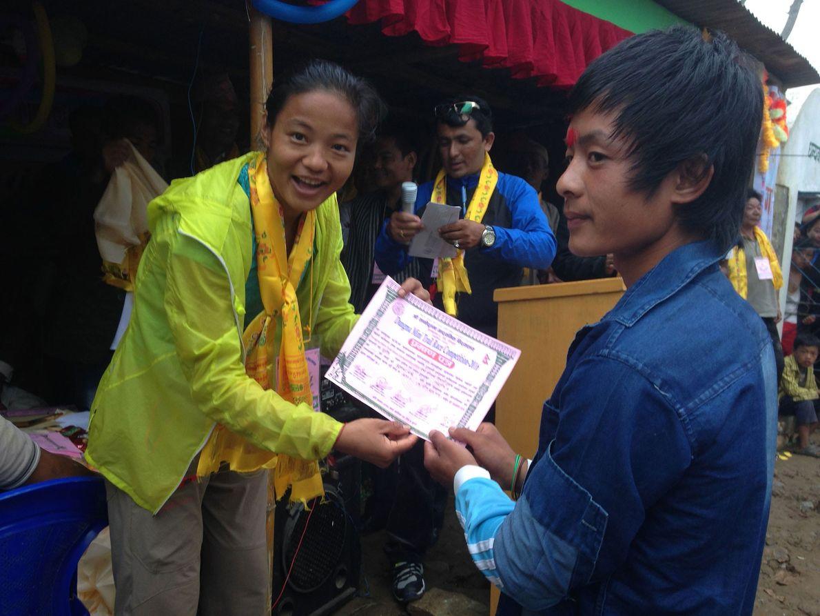 Imagen de la corredora Mira Rai otorgando sus certificados a los ganadores de la carrera en ...
