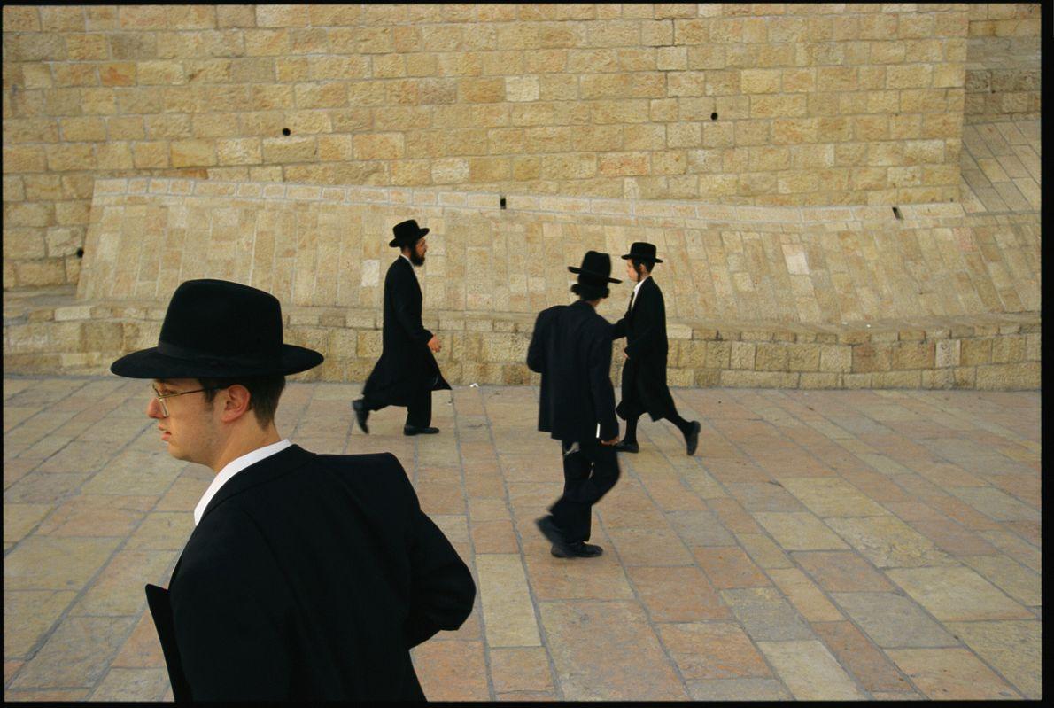 Imagen de cuatro judíos ortodoxos en su vestimente tradicional paseando por el Muro de las Lamentaciones ...