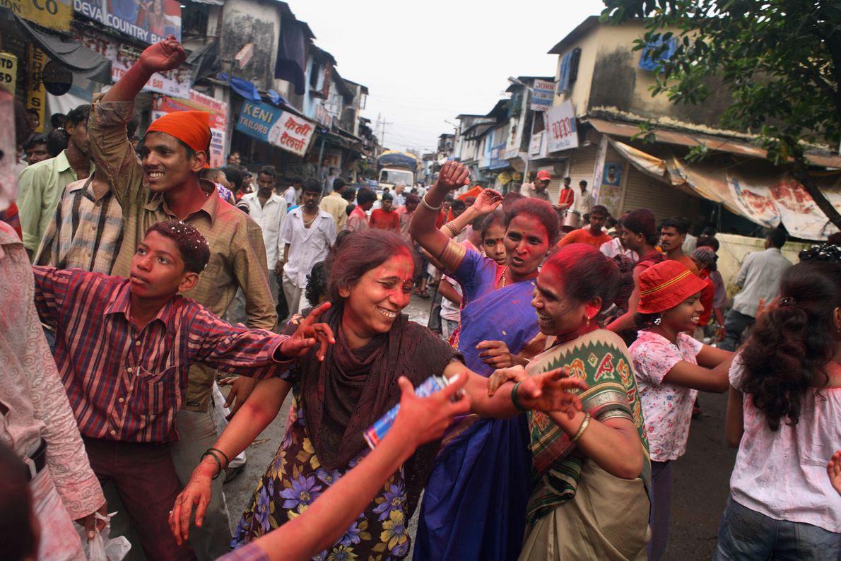 Imagen de gente lanzando polvos de colores para celebrar del festival en honor del dios Ganesha ...
