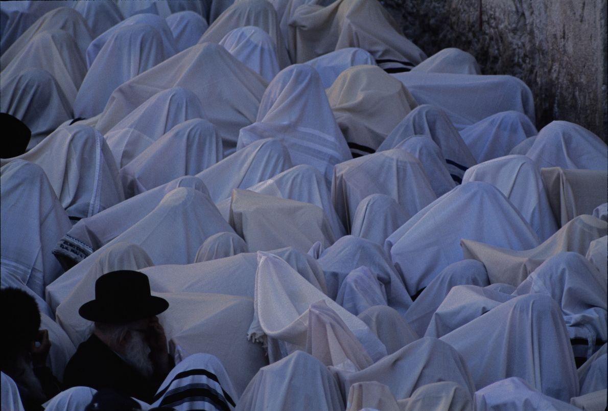 Imagen de personas cubiertas con mantones de oración arrodilladas en el Muro de las Lamentaciones