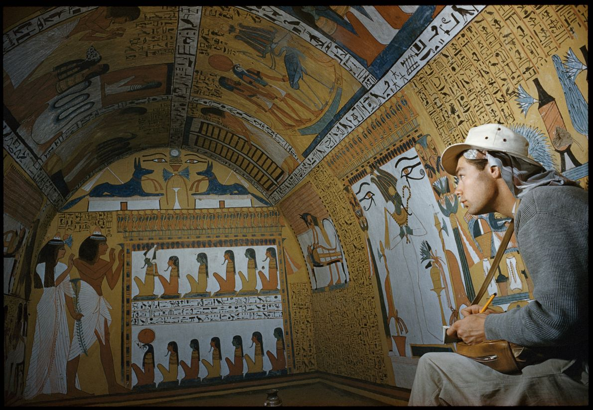 Imagen de una persona tomando notas de las elaboradas pinturas de una tumba del Antiguo Egipto