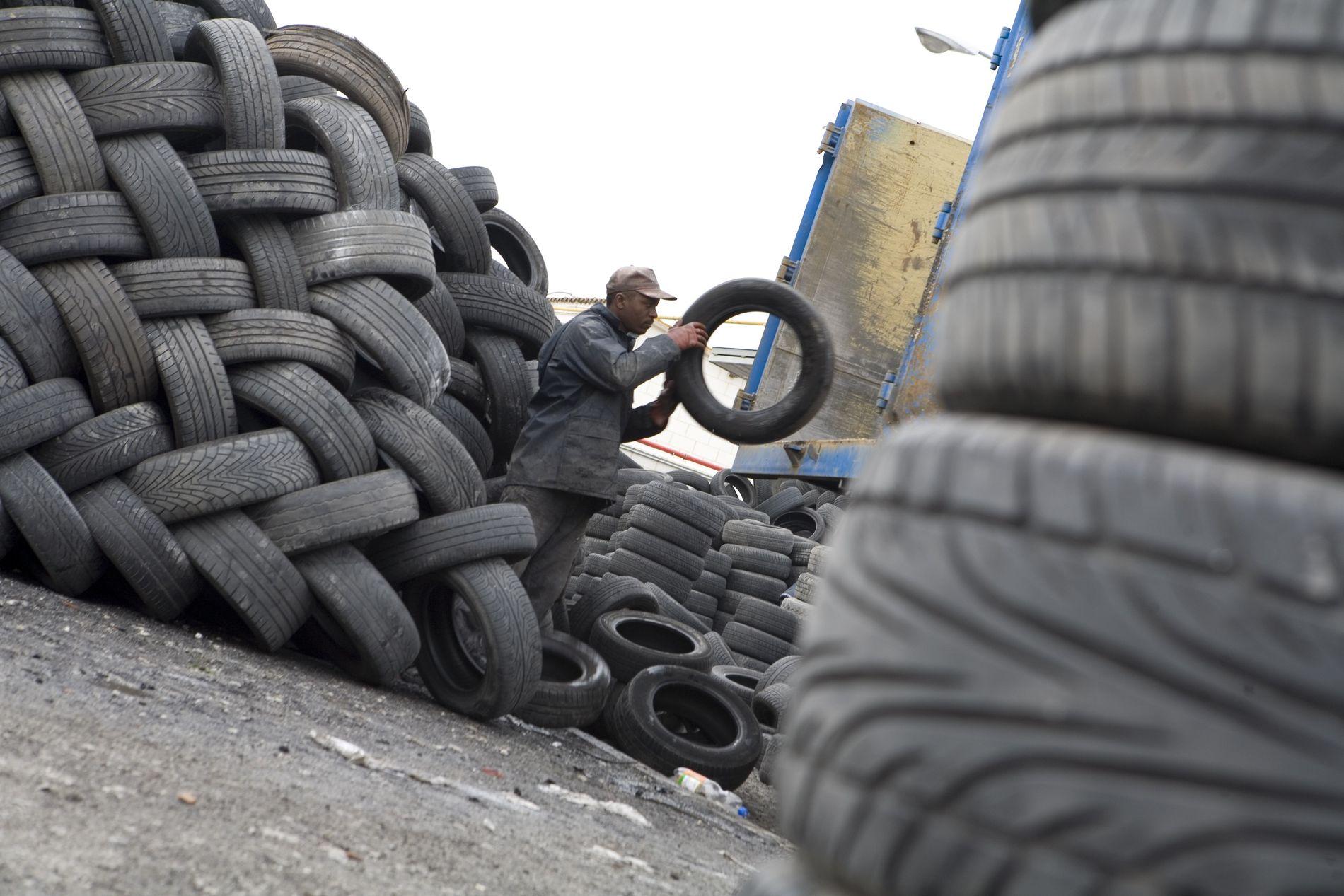 Un operario clasifica neumáticos para su posterior transformación.